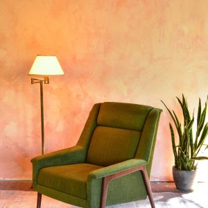 green arm chair in a living room with decor and plants