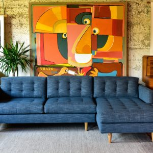 blue sofa with chaise in a living room with furniture and decor