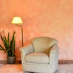 beige lounge chair in a living room with a pink wall and plants and decor