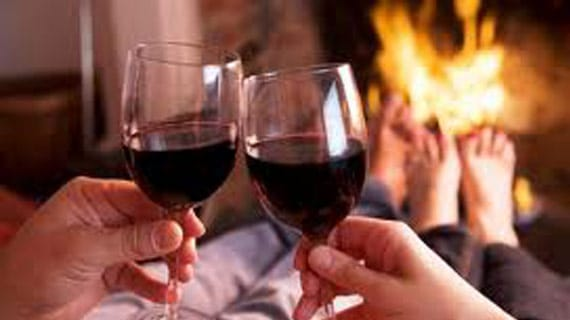Drinking wine in front of fireplace