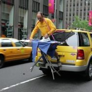 Man ironing on the back of a yellow cab