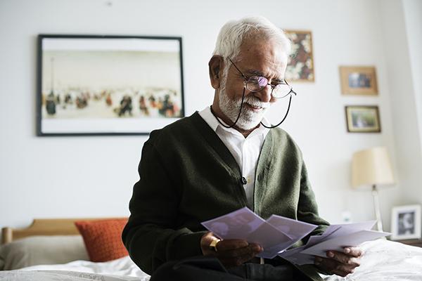Senior man wearing glasses looks at family photos