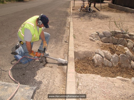 Tucson Concrete Cutting and Coring drilling 4-inch hole through curb. Drill is attached to hose to wet cut and reduce wear on drill bit.