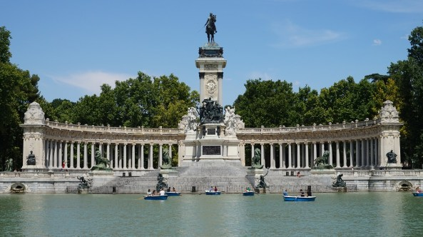 A picture of the large lake and Roman statue in the middle of Parque del Retiro in Madrid, Spain