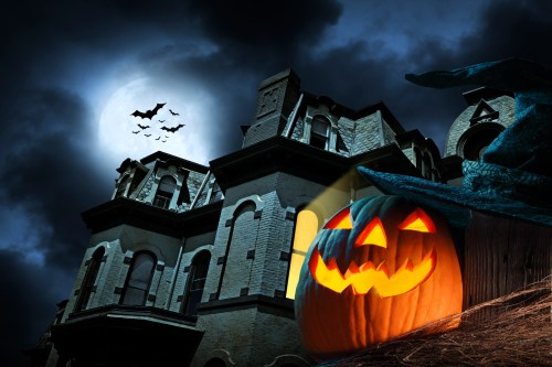 A pumpkin in front of a haunted house.