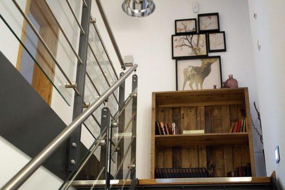 Beim Treppenaufstieg fällt der Blick auf das Regal aus altem, gemastertem Holz. Rustikal? Ja, aber edel. (Foto: Markus Burgdorf)