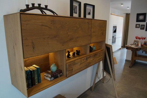 Das Wandregal im Wohnbereich wirkt ebenfalls durch das eher grobe Holz mit starker Maserung und Einschlüssen rustikal - auch wenn die Form modern ist. Man beachte den Kerzenständer oben links, der das Hirschmotiv aufnimmt. (Foto: Markus Burgdorf)