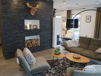 Ein Elch aus Holz blickt von der Wandscheibe im Wohnzimmer, deren Nischen Holz und Familienfotos aufnehmen. (Foto: Markus Burgdorf)