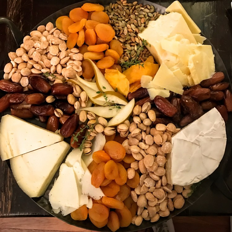 Appetizers can be as simples as dried fruits, nuts, and cheese. Filling your platter to the brim can make an impressive statement.
