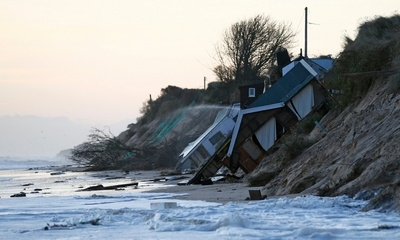 Collapsed houses lie on the beach after a storm surge in Hemsby, eastern England, 6th December 2013. Parts of England's east coast, from Yorkshire to Essex are vulnerable to stronger storms and rising sea levels due to climate change. Photograph: Darren Staples/Reuters