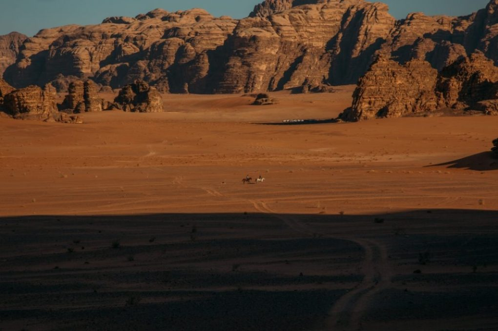 A couple riding horses through Wadi Rum.