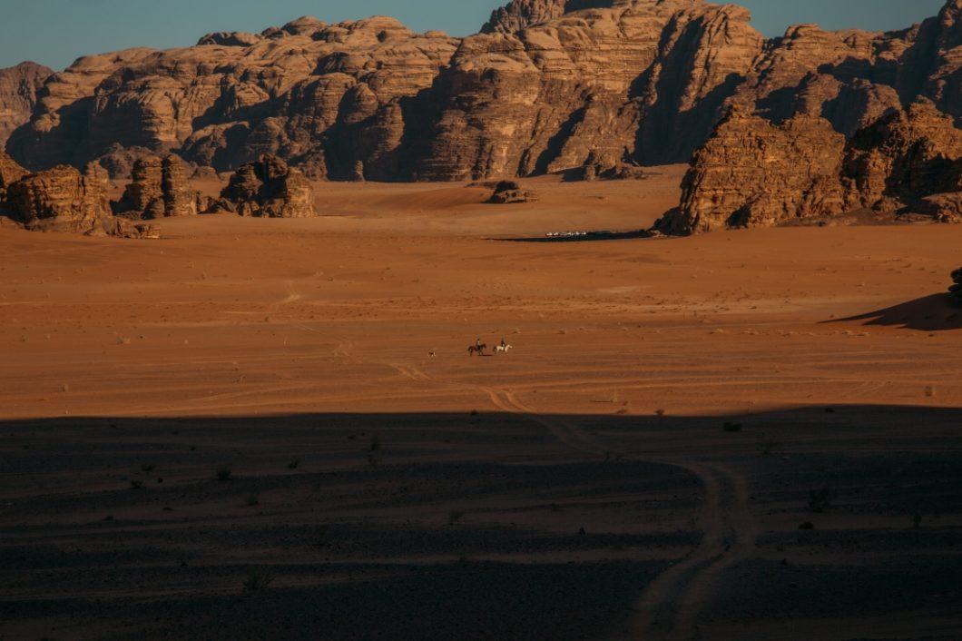 A couple riding horses through Wadi Rum.