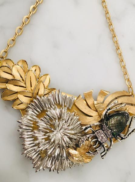 Gorgeous collage, original by artist. Midcentury vintage pieces form a stunning unique collage of dangerous beauty. A stag beetle approaches a lovely starflower in a garden. 22ct goldplate chain.