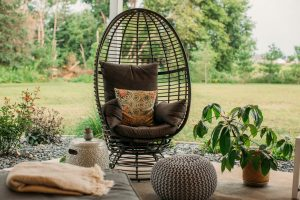 Grey egg chair with pouf ottoman in a cozy boho chic outdoor living space