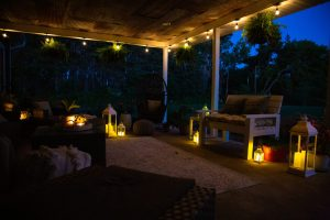 Outdoor boho chic patio at night with string lights and decorative lanterns