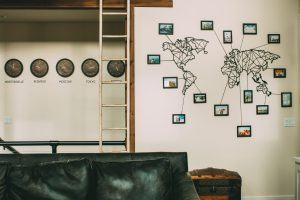 Metal world map laser cut with photo frames and lines pointing to destinations + time zone clocks wall