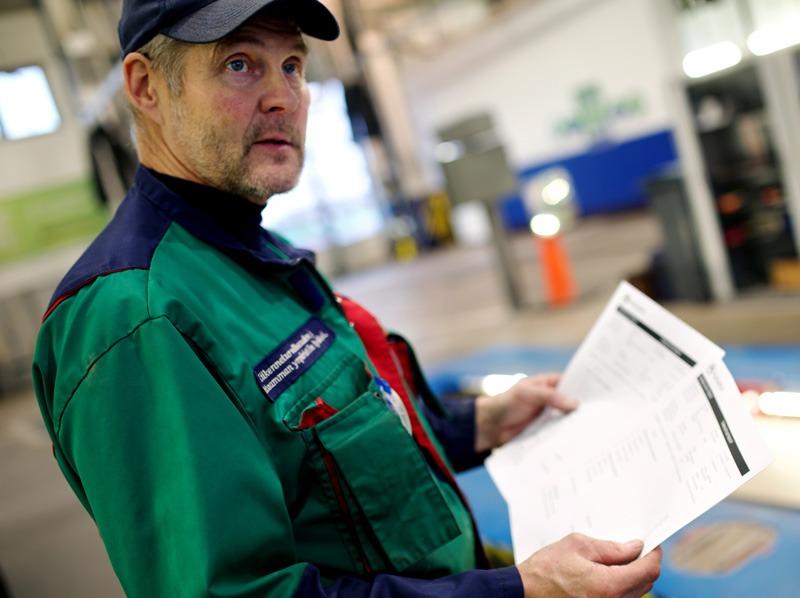 Autotohtorilla on kädessään tarkastusraportit.