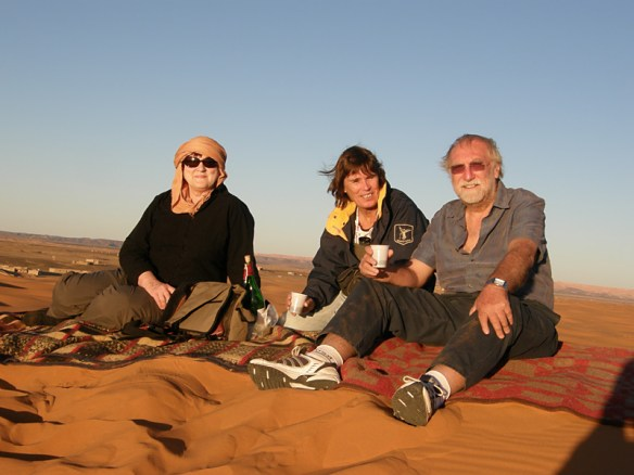 Melita, Wendy and Phil sharing a glass of wine while watching the sun set over the sand dunes near Xaluca, Morocco.