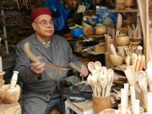 Tunisian shopkeeper at a stall in Gabes selling wooden goods.