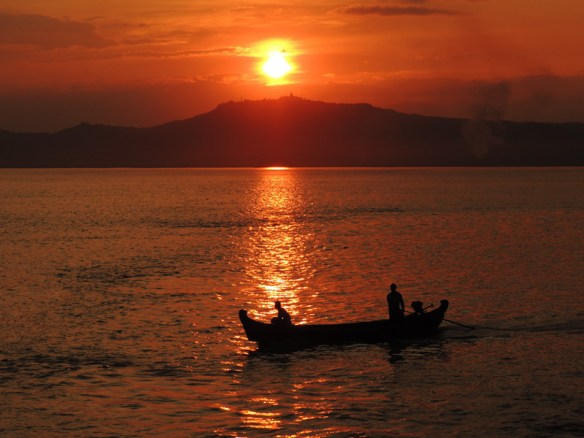 A boat silhouetted at sunset on the Irrawaddy River near Bagan, Myanmar.