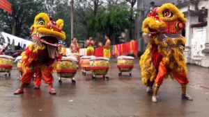 The unicorn and the lion dancing to the sound of drums and cymbals at Bat Trang, North Vietnam.
