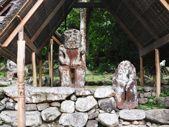 These tiki statues (the male is standing, the female sitting) are protected from the elements by recently erected thatched roofs at Te I'ipona archaeological site near Puamau village on Hiva Oa, Marquesas Islands.