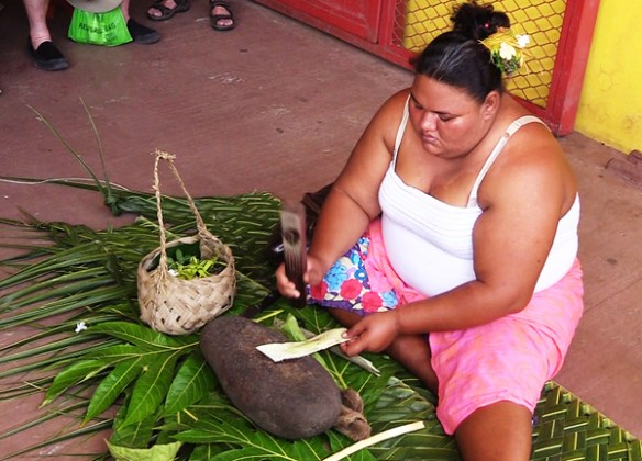 A local mama shows tourists how tapa cloth is made from mulberry bark in Omoa village on Fatu Hiva, Marquesas Islands.
