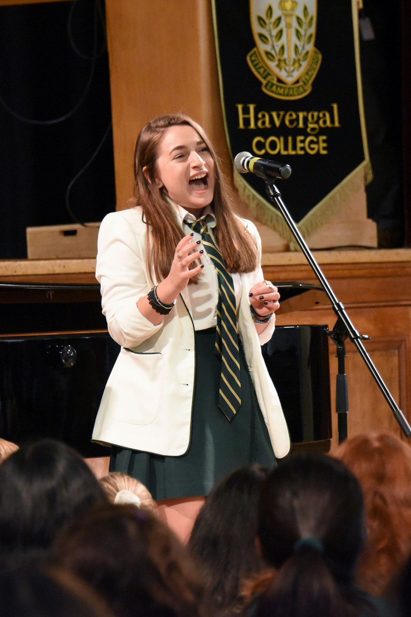 A student singing in front of a crowd in the Brenda Robson Hall.
