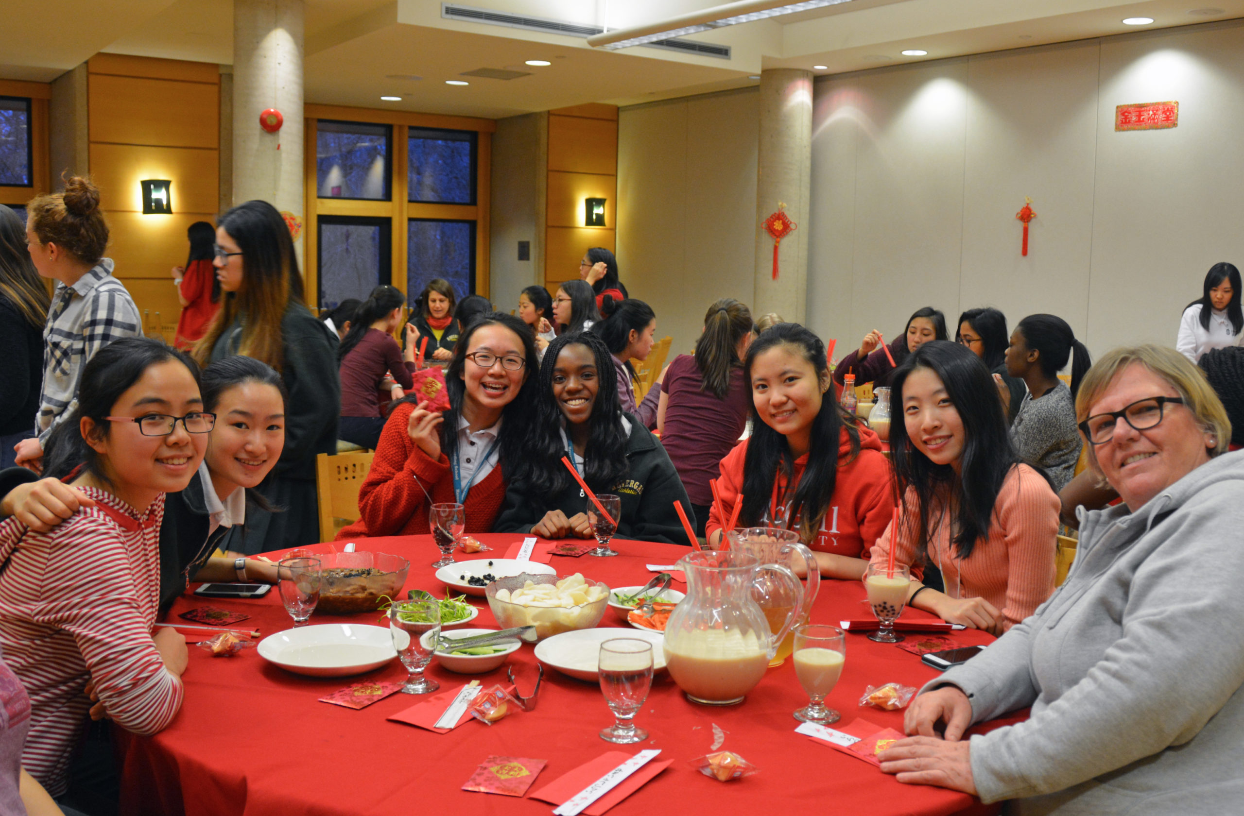 A group of students and a Don sit at a table for a Lunar New Year dinner.