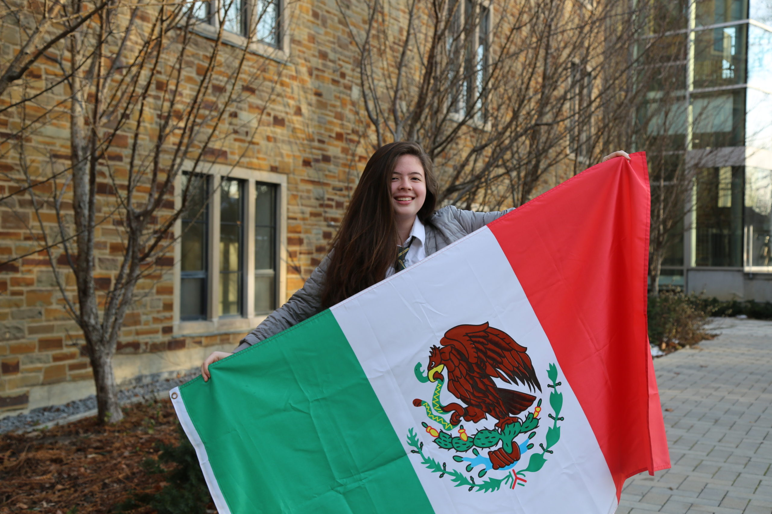 A student outside the Upper School smiles while holding a Mexican flag.