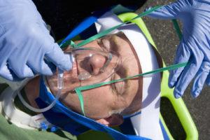 Paramedic putting mask on man on stretcher, close-up