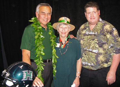 Norm Chow, Virginia Hinshaw and Jim Donvan standing by UH football helmet