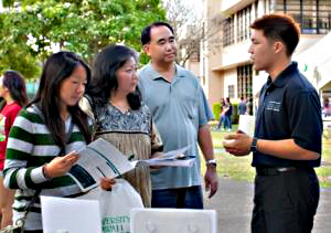 A Shidler College of Business representative speaks with a family