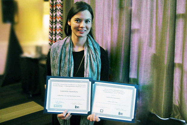 student holding two certificates