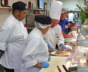 Jay Kido and classmate watch as instructor puts together a dish