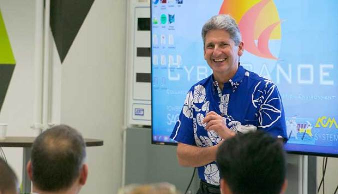 David Lassner in front of a presentation board