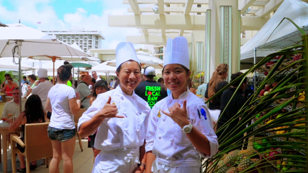 Two culinary students flashing shaka at an event