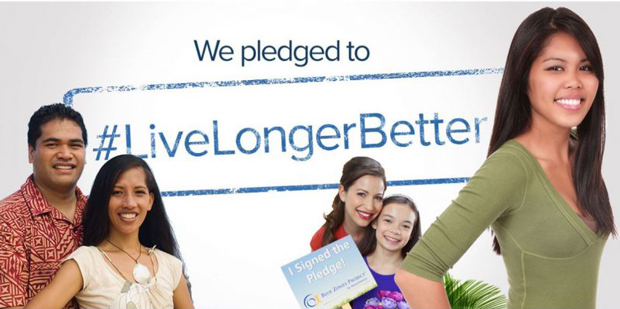 smiling people with banner that says, 'We pledged to live longer better