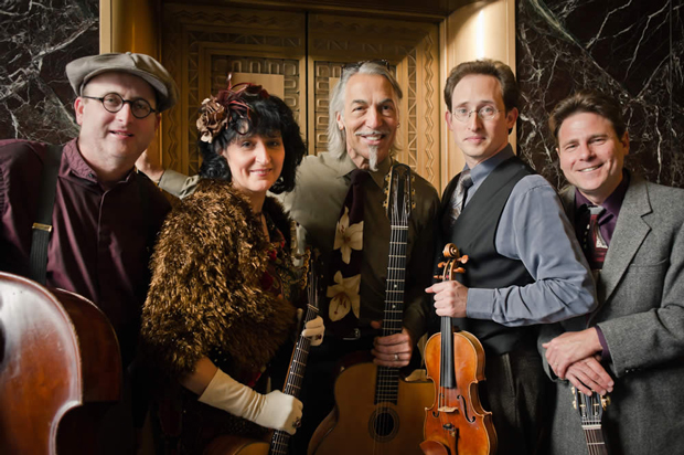 Four men and one woman smiling and posing with string instruments