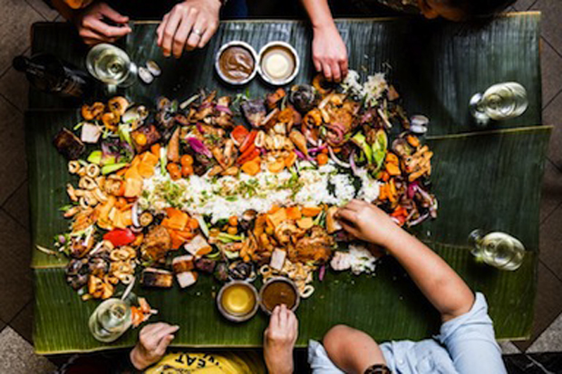 table with food on banana leaf