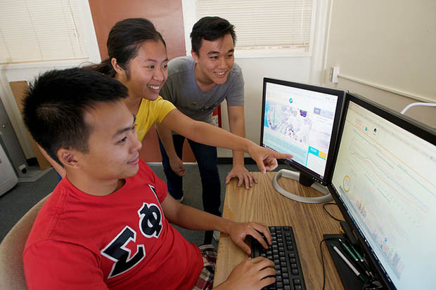 Students around two computer screens