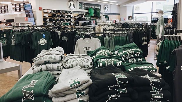 A table of folded UH Manoa athletics merchandise