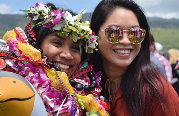 U H graduate with lei and friend