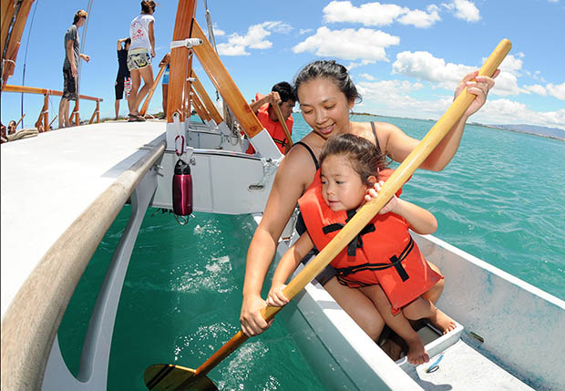 Woman and child in a life vest holding a paddle