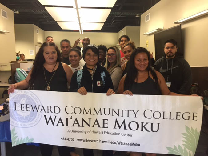 Students hold up a Leeward C C Waianae Moku banner