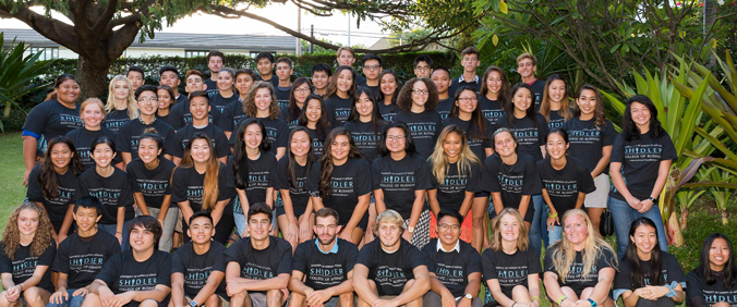 rows of posed smiling students wearing the same Shidler t-shirt