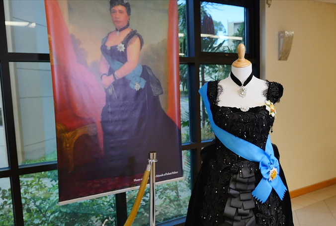 black ribbon dress with blue sash displayed next to the portrait of the queen wearing the original
