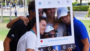 Five men take a picture with an instagram cutout frame.