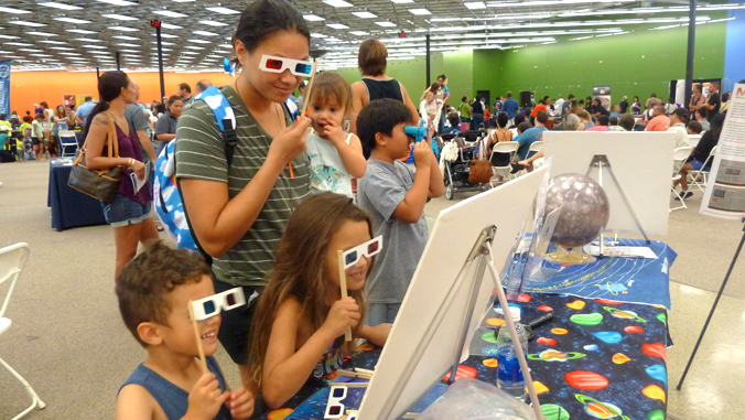 family using viewing glasses to look at exhibit