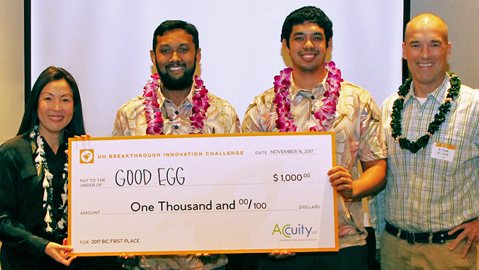 four people holding big check